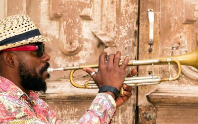 Cuban musician playing trumpet standing in front of the old door in Havana, Cuba