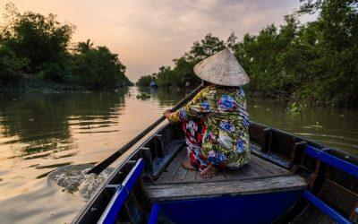 Vietnamese woman rowing a boat, Mekong River Delta, Vietnam