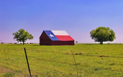 A barn in rural Texas with the state flag painted on the roof