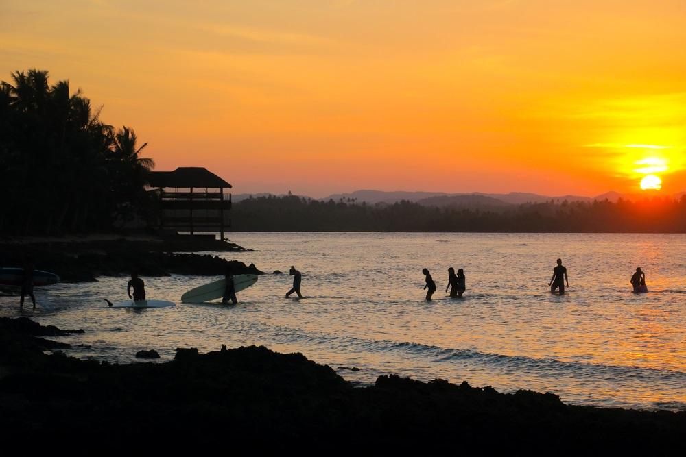 Surfisti al tramonto a Siargao, Filippine
